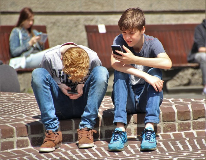 2 boys and 1 girl looking at phones