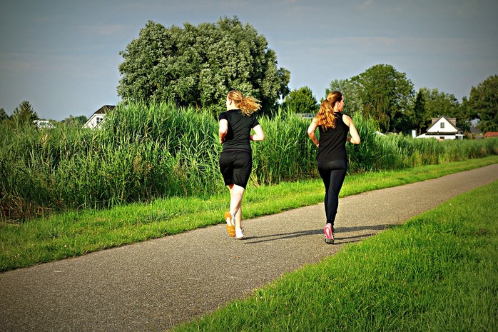 2 women jogging on a path outside