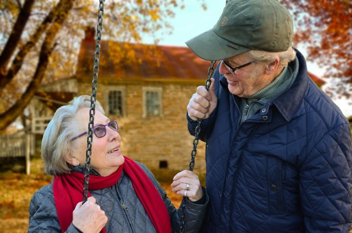 elderly couple talking near a swing