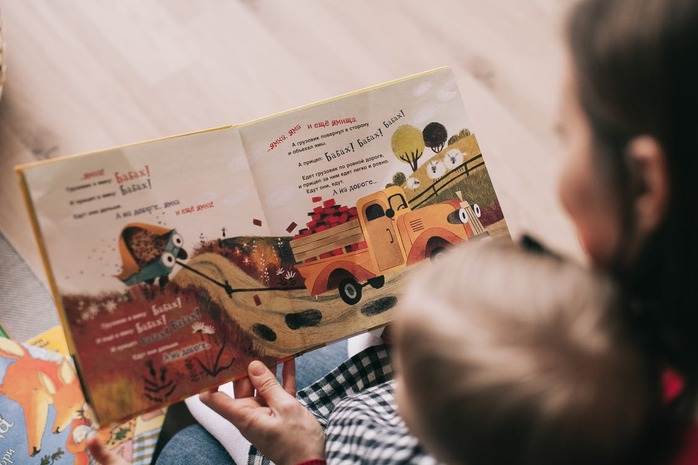 parent reading a book to her child