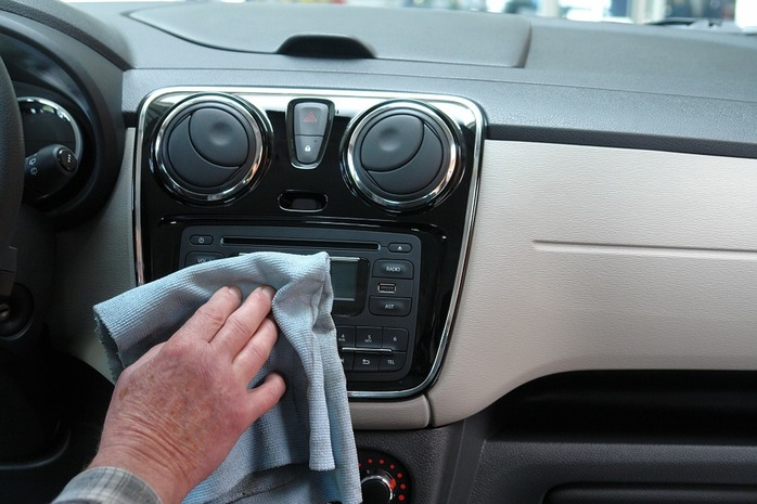 person wiping down the inside of the car
