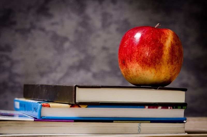 red apple on top of books