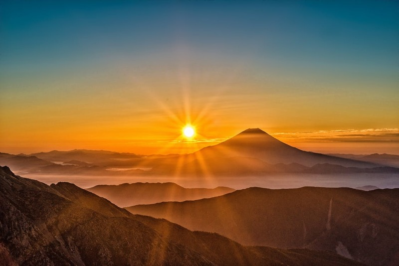 sun shining in the sky over mountains  - How to Shine on a Dark Day