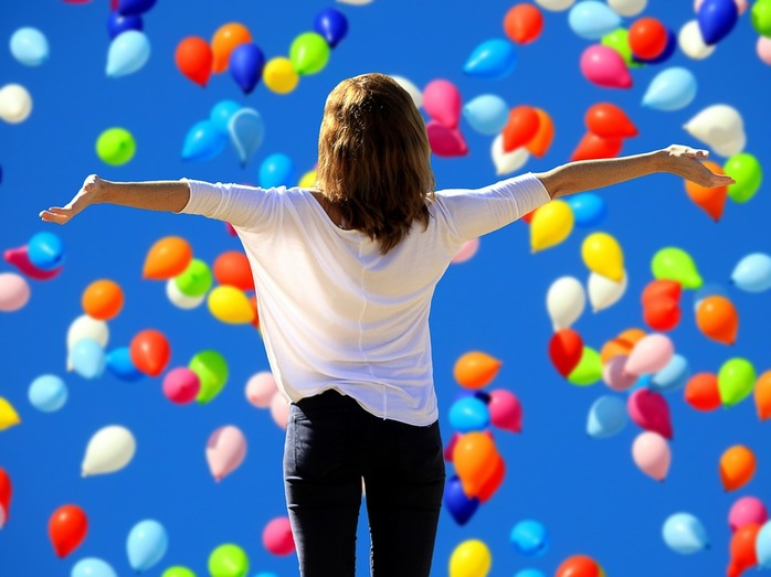woman holding her hands up in the air filled with balloons