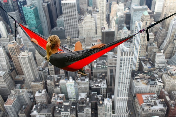 woman laying in a hammock looking over a city