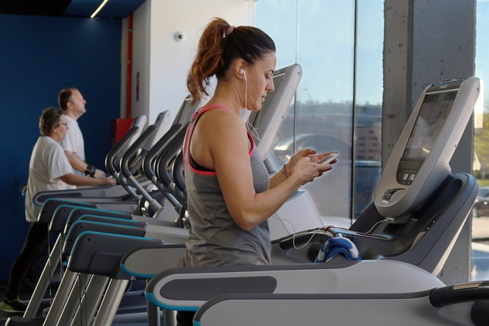 woman on treadmill looking at her phone