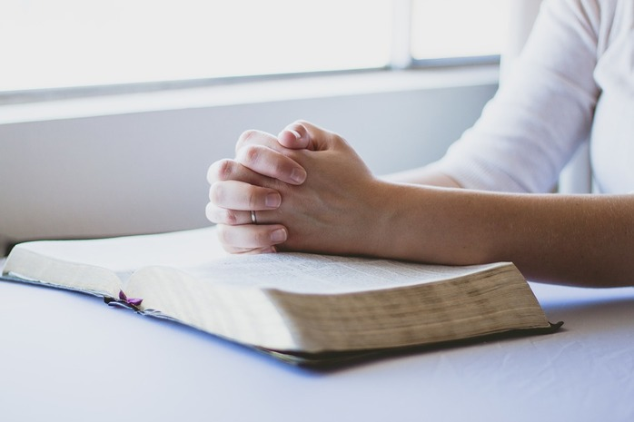 woman praying and reading the Bible