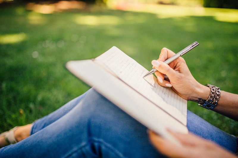 woman sitting in the grass writing in her journal