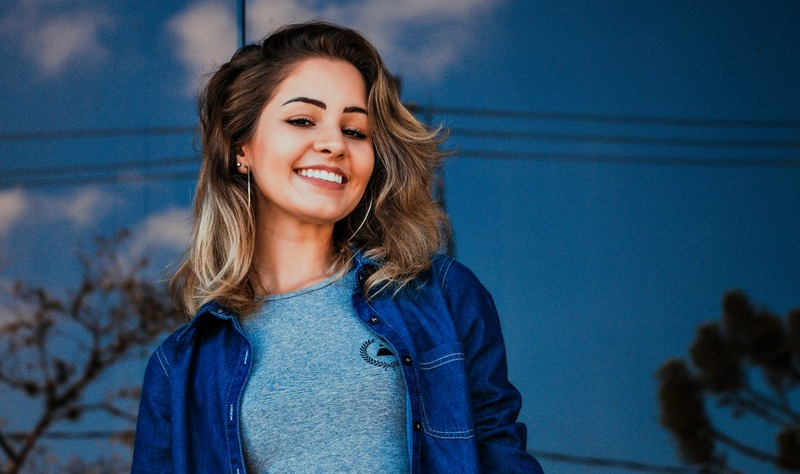 woman smiling with blue background  - Healthy Teeth and a Perfect Smile