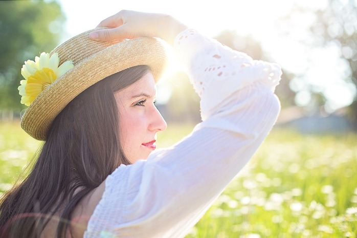 woman standing in sunshine touching her hat