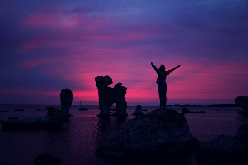 woman standing on a rock with hands up  - Resilience to Endure Life's Challenges