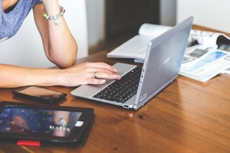 woman typing on laptop with open books  - Career Changes
