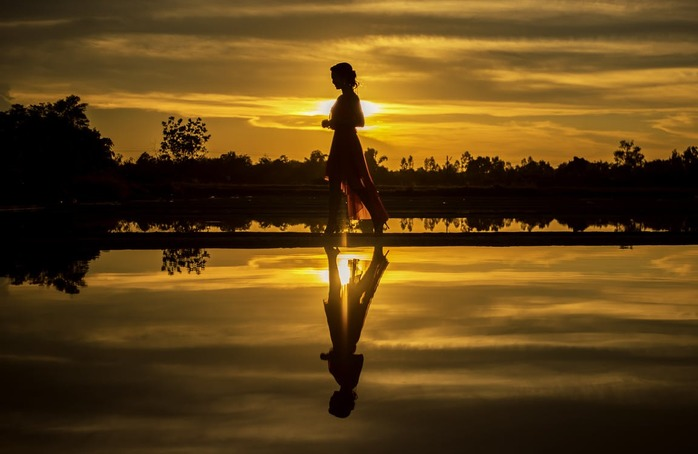 woman walking along side water