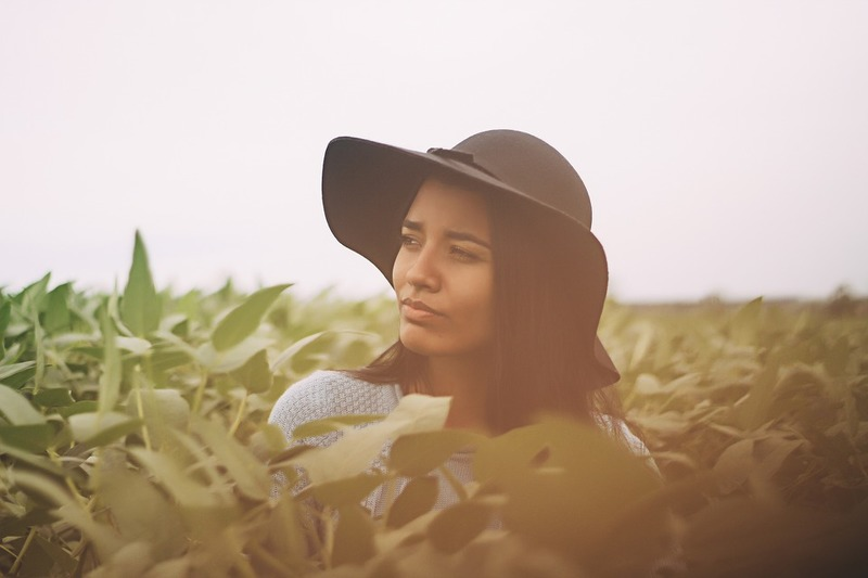 woman wearing a black hat standing outdoors in a field  - How to Reverse Sun Damaged Skin