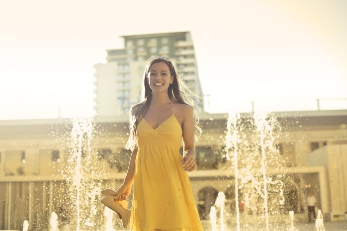 woman wearing yellow dress standing in front of fountain
