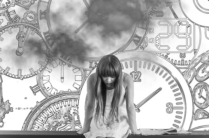 worried woman sitting in front of many clocks